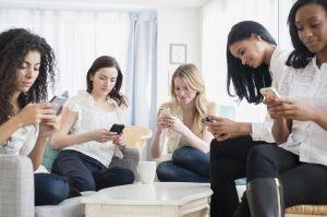 Women using cell phones in living room