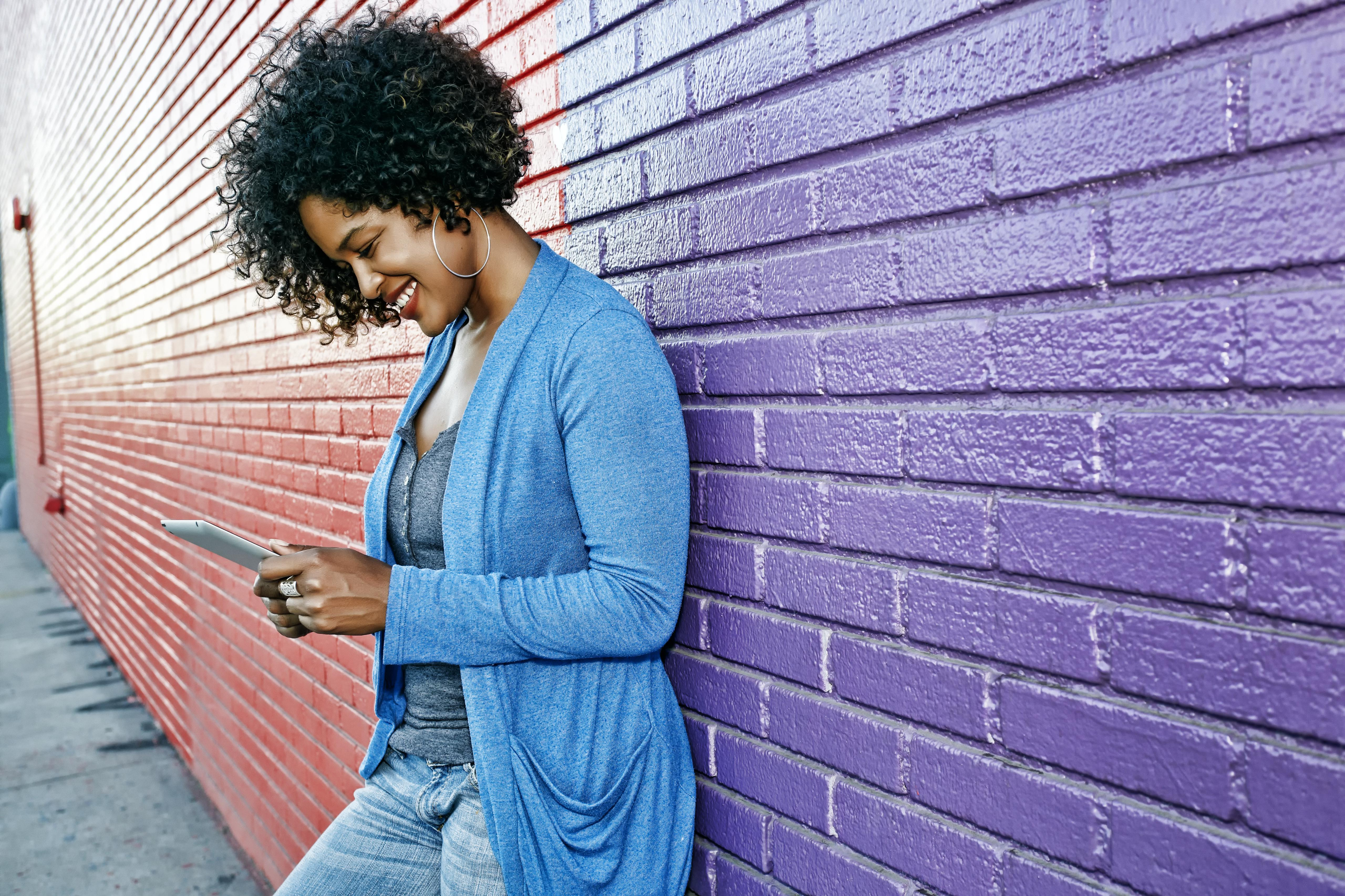 Mixed race woman with cell phone standing by colorful wall