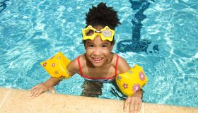 Girl with floaties and goggles in swimming pool