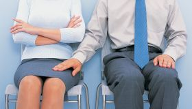 Mid Section View of a Businessman Touching the Thigh of a Businesswoman Sitting by Him